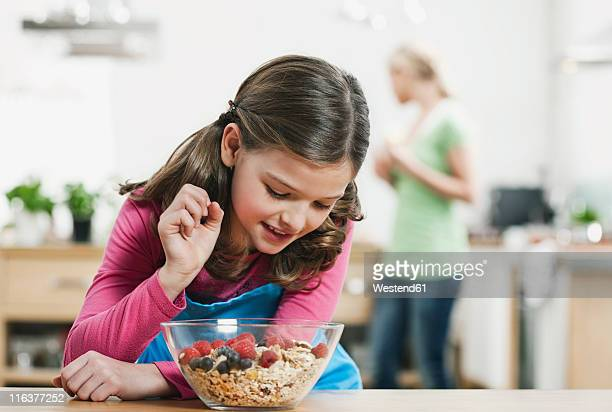 Germany, Cologne, Girl looking at muesli in bowl, mother in background