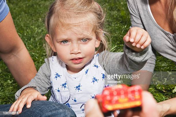 Germany, Cologne, Girl (2-3 Years) looking at toy with parents
