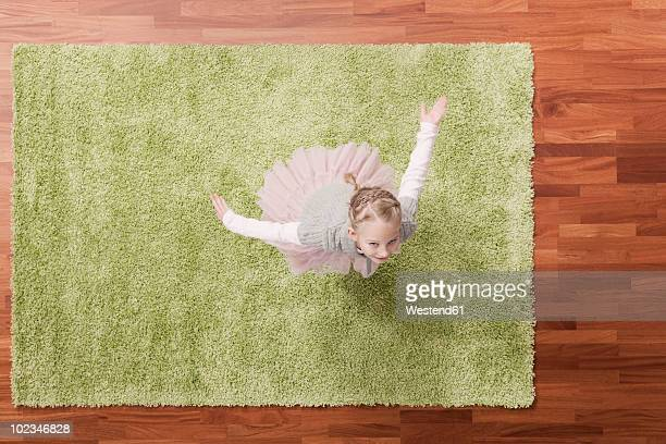 germany, cologne, girl (6-7) playing on carpet, looking up, elevated view - teppich stock-fotos und bilder
