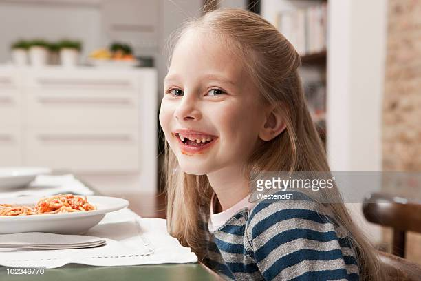 Germany, Cologne, Girl (6-7) sitting at table, smiling, portrait, close-up