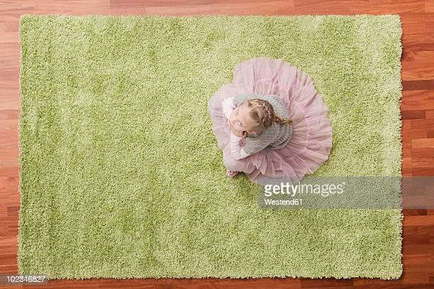 Germany, Cologne, Girl (6-7) sitting on carpet, looking up, elevated view