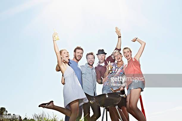 Germany, Cologne, Group of people gathered around barbecue