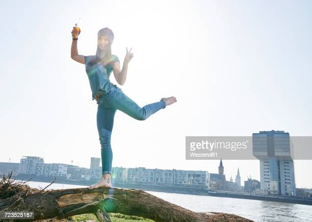 Germany, Cologne, happy young woman with beer bottle at River Rhine