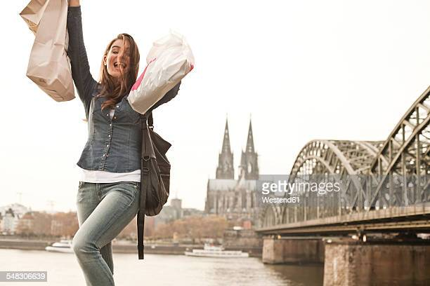 Germany, Cologne, happy young woman with shopping bags