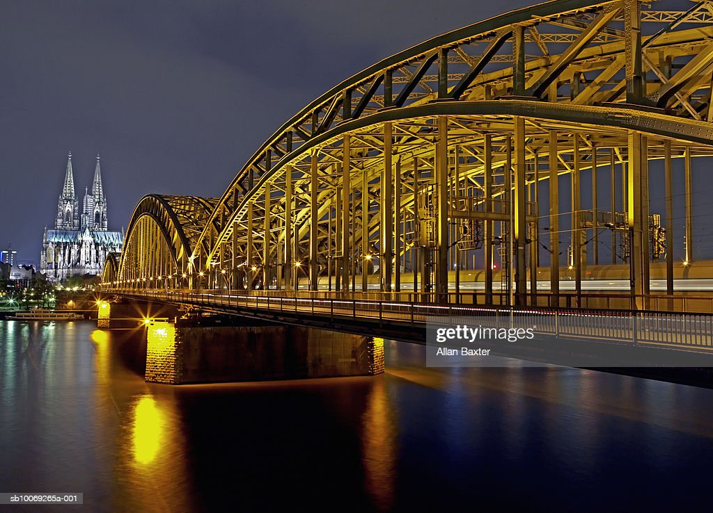 Germany, Cologne, Hohenzollernbrucke bridge and cathedral illuminated at night : Stockfoto