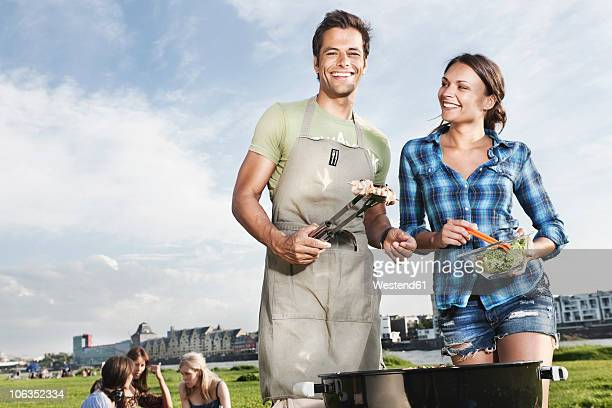 Germany, Cologne, Man and woman barbecueing with friends in background