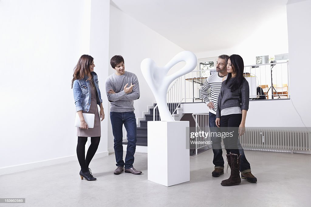 Germany, Cologne, Man and woman standing in art gallery, smiling : ストックフォト