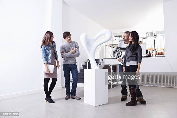 germany, cologne, man and woman standing in art gallery, smiling - sculptuur stockfoto's en -beelden