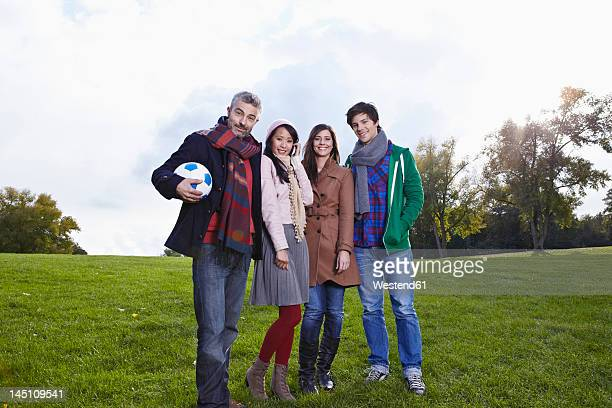 Germany, Cologne, Man and woman standing in park, smiling, portrait
