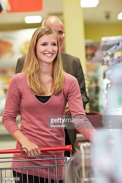 Germany, Cologne, Man and woman waiting in supermarket, smiling