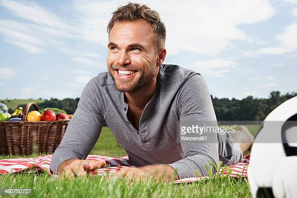 Germany, Cologne, Man lying on picnic blanket, smiling