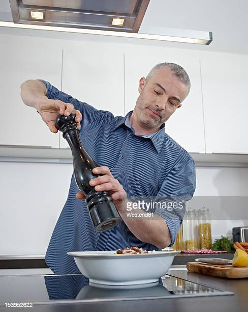 Germany, Cologne, Mature man cooking food in kitchen