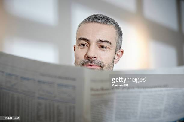 Germany, Cologne, Mature man reading newspaper