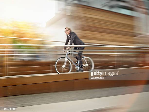 Germany, Cologne, Mature man riding bicycle