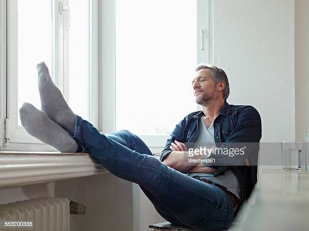 Germany, Cologne, Mature man sitting at window, eyes closed