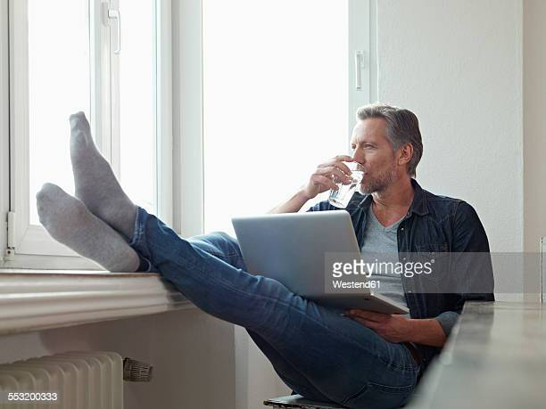 Germany, Cologne, Mature man sitting at window using laptop, feet up