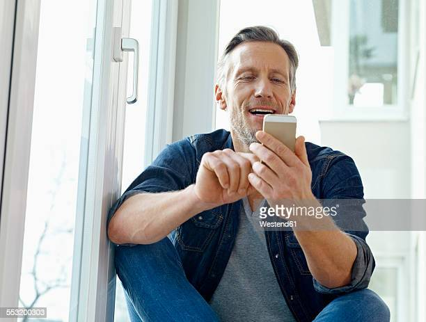 Germany, Cologne, Mature man sitting at window using smart phone