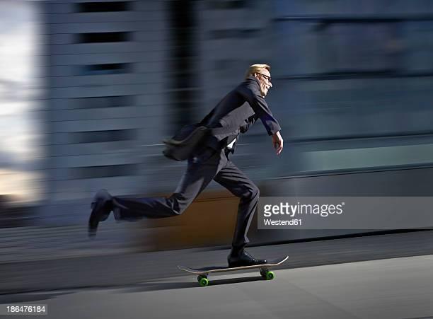 germany, cologne, mature man skating on road - skateboard stock-fotos und bilder