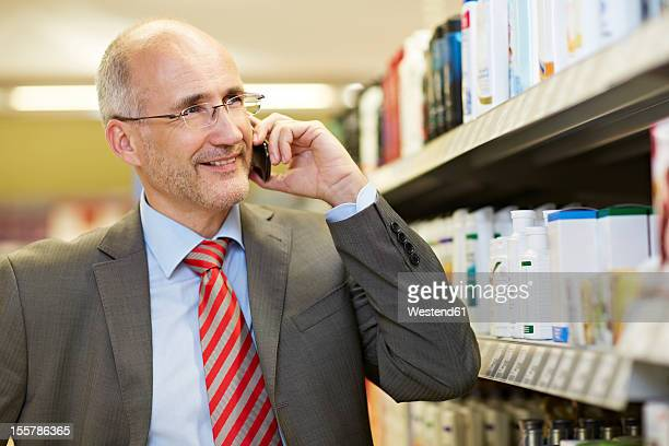 Germany, Cologne, Mature man talking on cell phone in supermarket, smiling