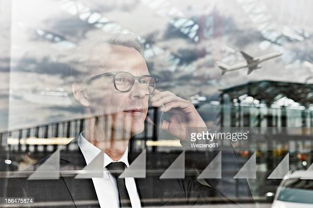 Germany, Cologne, Mature man talking on phone at airport
