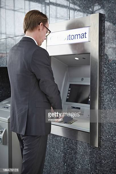 Germany, Cologne, Mature man using cash dispenser machine at airport
