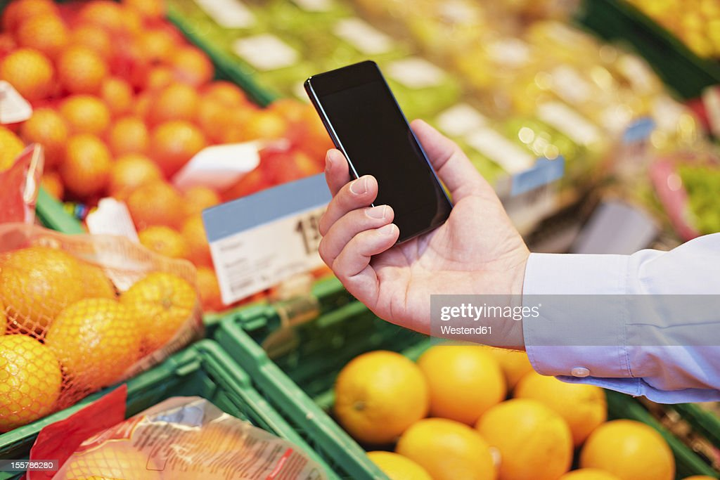 Germany, Cologne, Mature man using smart phone in supermarket : Stock Photo