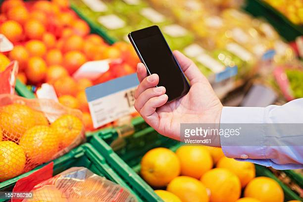 Germany, Cologne, Mature man using smart phone in supermarket