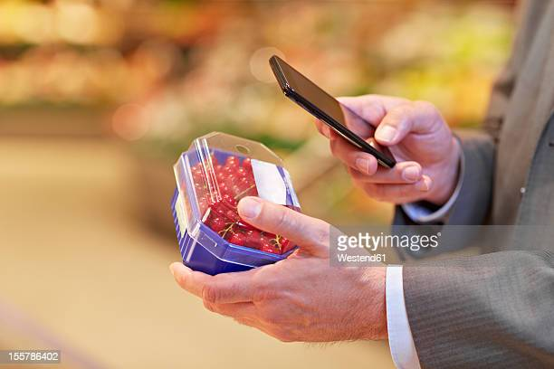 germany, cologne, mature man with redcurrant and smart phone in supermarket - blackberry fruit stock pictures, royalty-free photos & images