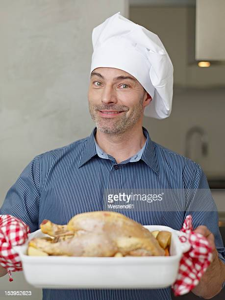 Germany, Cologne, Mature man with roast chicken, smiling, portrait