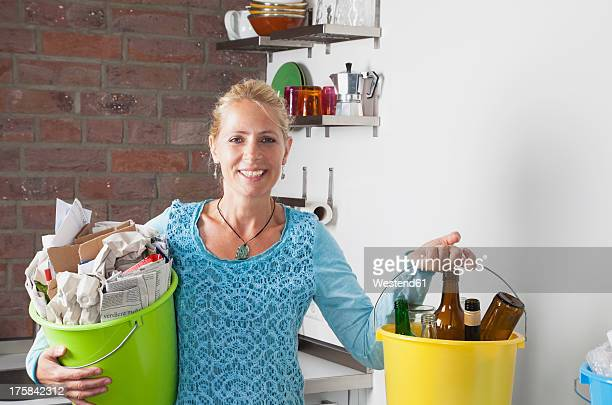 germany, cologne, mature woman carrying buckets with household garbage in kitchen - daily bucket stock pictures, royalty-free photos & images