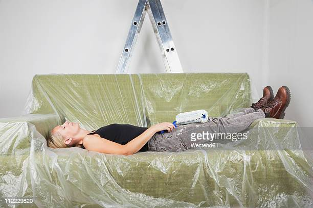 Germany, Cologne, Mature woman resting on plastic foiled sofa holding paint roller