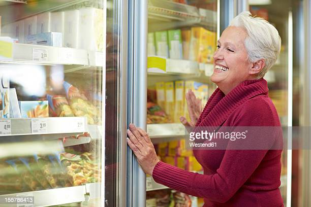 Germany, Cologne, Mature woman standing at freezer in supermarket