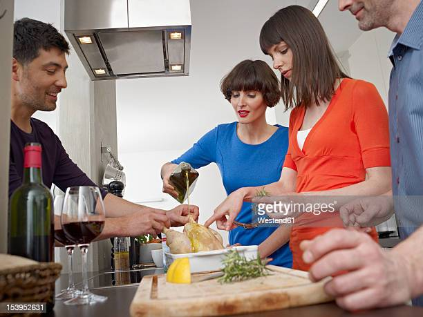 Germany, Cologne, Men and women cooking together in kitchen