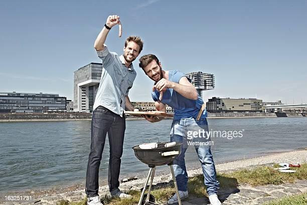 Germany, Cologne, Men grilling sausage