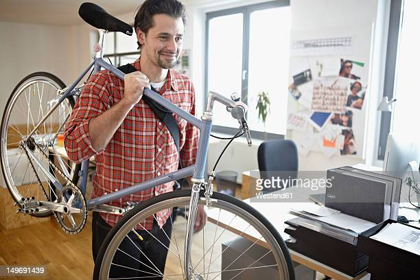 Germany, Cologne, Mid adult man carrying bicycle, smiling