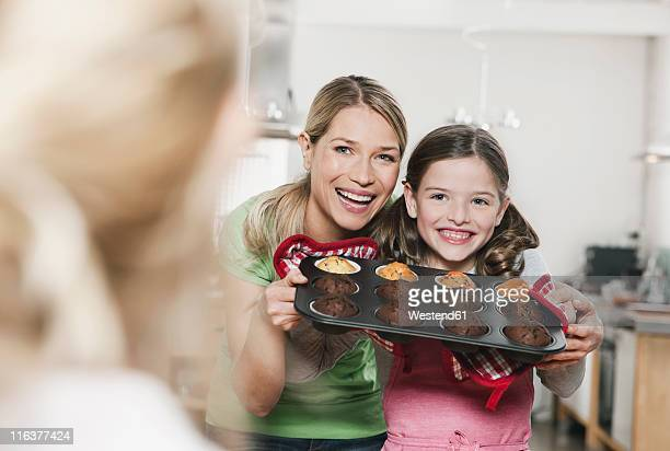 Germany, Cologne, Mother and daughter holding cup cakes in baking tray, smiling