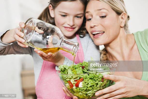 Germany, Cologne, Mother and daughter preparing salad