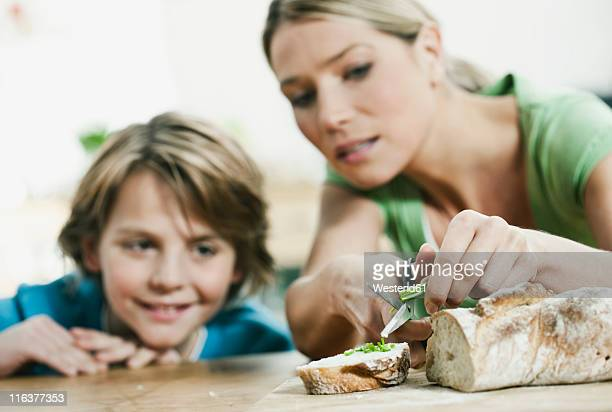 germany, cologne, mother and son cutting bread in kitchen - accompagnement photos et images de collection