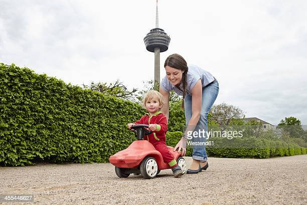 Germany, Cologne, Mother carrying daughter in toy car, smiling