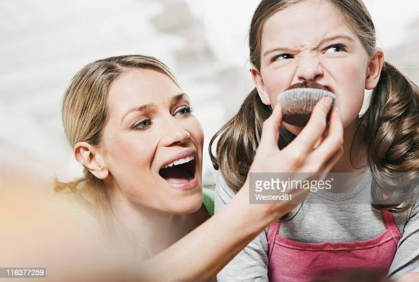 Germany, Cologne, Mother feeding cup cake to daughter