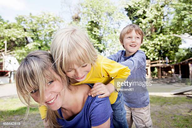 Germany, Cologne, Mother playing with children in playground