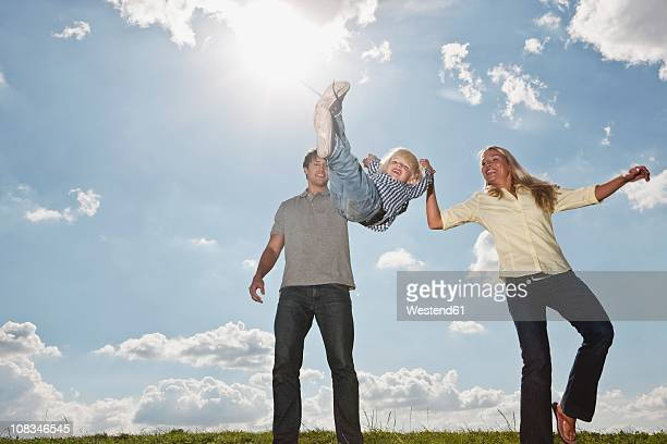 Germany, Cologne, Parents playing with their son (2-3 Years), smiling