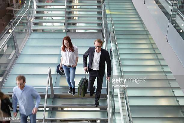 Germany, Cologne, People walking down stairs with baggage at airport