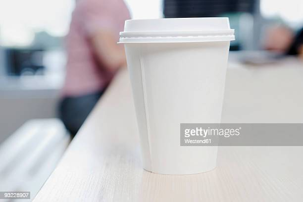 Germany, Cologne, Plastic cup on counter, people in background