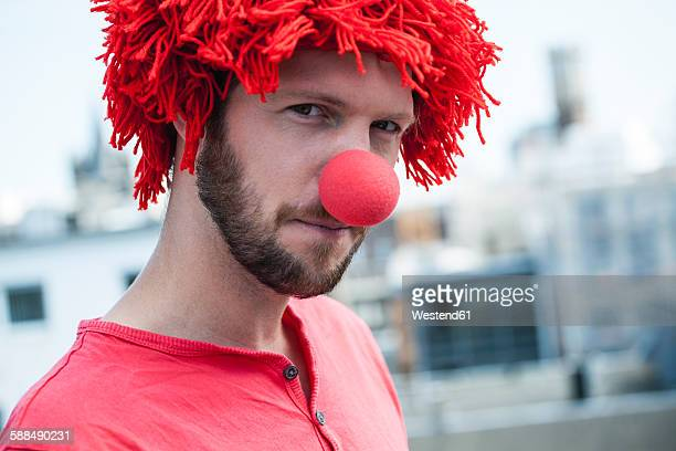 Germany, Cologne, portrait of bearded young man wearing clowns nose and red wig