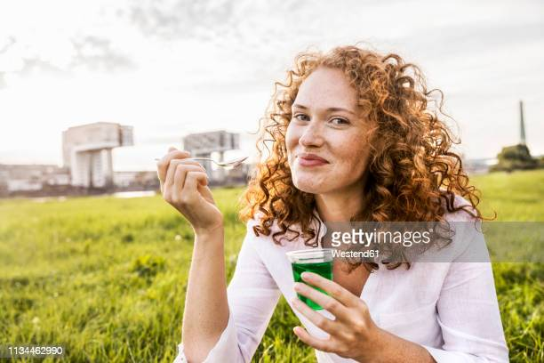 germany, cologne, portrait of happy young woman eating jelly on meadow - mousse dessert stock pictures, royalty-free photos & images