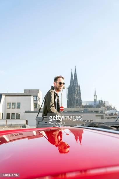 germany, cologne, portrait of smiling mature man with his parked sports car - barba por fazer imagens e fotografias de stock