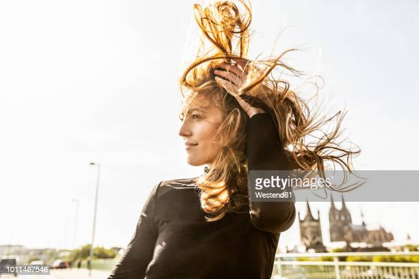 germany, cologne, portrait of smiling woman with blowing hair - wind stockfoto's en -beelden