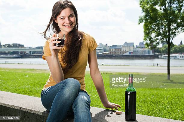 Germany, Cologne, portrait of smiling young woman sitting in front of Rhine River drinking red wine