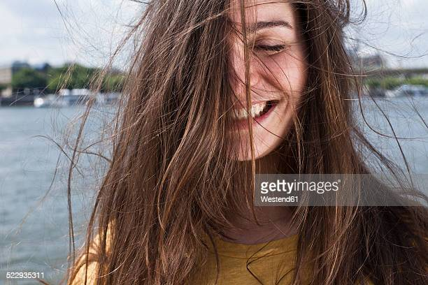 Germany, Cologne, portrait of smiling young woman with blowing hair standing in front of Rhine River